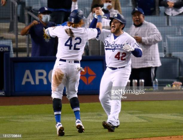 Max Muncy of the Los Angeles Dodgers celebrates his three run homerun with Justin Turner, to take a 6-5 lead over the Colorado Rockies, during the...