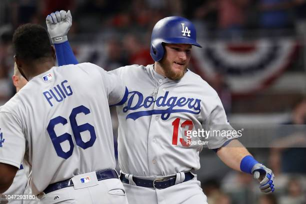 Max Muncy of the Los Angeles Dodgers celebrates with Yasiel Puig after hitting a solo home run in the fifth inning against the Atlanta Braves during...