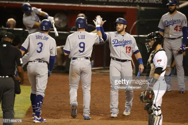Max Muncy of the Los Angeles Dodgers high fives Gavin Lux and Chris Taylor after Lux hits a a three-run home run against the Arizona Diamondbacks...