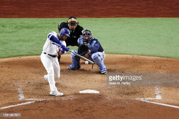 Max Muncy of the Los Angeles Dodgers hits into an RBI fielders choice against the Tampa Bay Rays during the fifth inning in Game One of the 2020 MLB...
