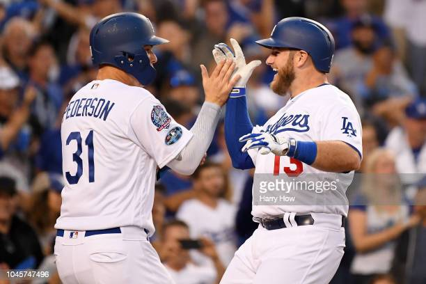 Max Muncy of the Los Angeles Dodgers is congratulated by his teammate Joc Pederson after his second inning 3 RBI home run against the Atlanta Braves...