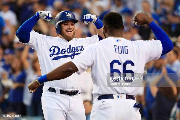 Max Muncy of the Los Angeles Dodgers is congratulated by his teammate Joc Yasiel Puig after his second inning three run home run against the Atlanta...