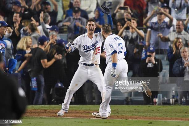 Max Muncy of the Los Angeles Dodgers is congratulated by his teammate Cody Bellinger after his eighteenth inning walkoff home run to defeat the the...