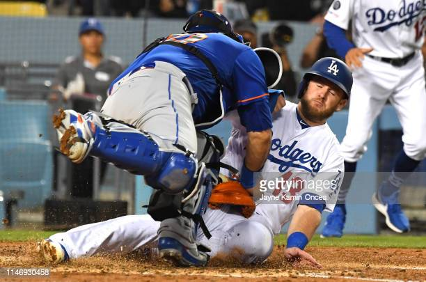 Max Muncy of the Los Angeles Dodgers is safe at home as he beats the tag by Wilson Ramos of the New York Mets scoring on a single by Justin Turner of...