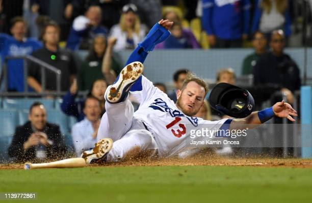 Max Muncy of the Los Angeles Dodgers is safe at home as he gets past Francisco Cervelli of the Pittsburgh Pirates to score a run on a sacrifice fly...