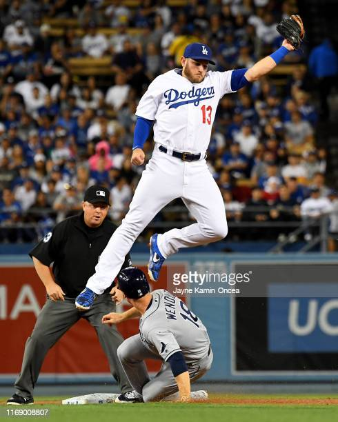 Max Muncy of the Los Angeles Dodgers leaps for a high throw from as Joey Wendle of the Tampa Bay Rays is safe at second with a stolen base in the...