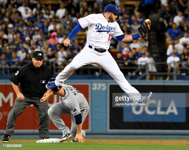 Max Muncy of the Los Angeles Dodgers leaps for a high throw from Will Smith of the Los Angeles Dodgers as Joey Wendle of the Tampa Bay Rays is safe...