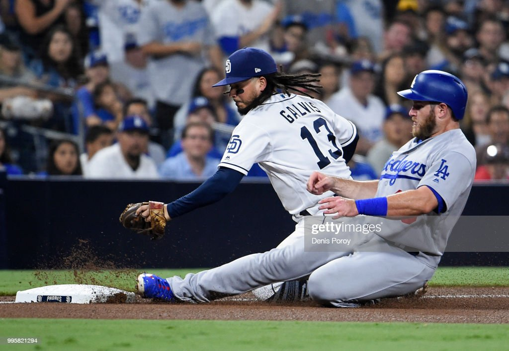 Max Muncy #13 of the Los Angeles Dodgers slides into third base ahead of the tag of Freddy Galvis #13 of the San Diego Padres during the seventh inning of a baseball game at PETCO Park on July 10, 2018 in San Diego, California.