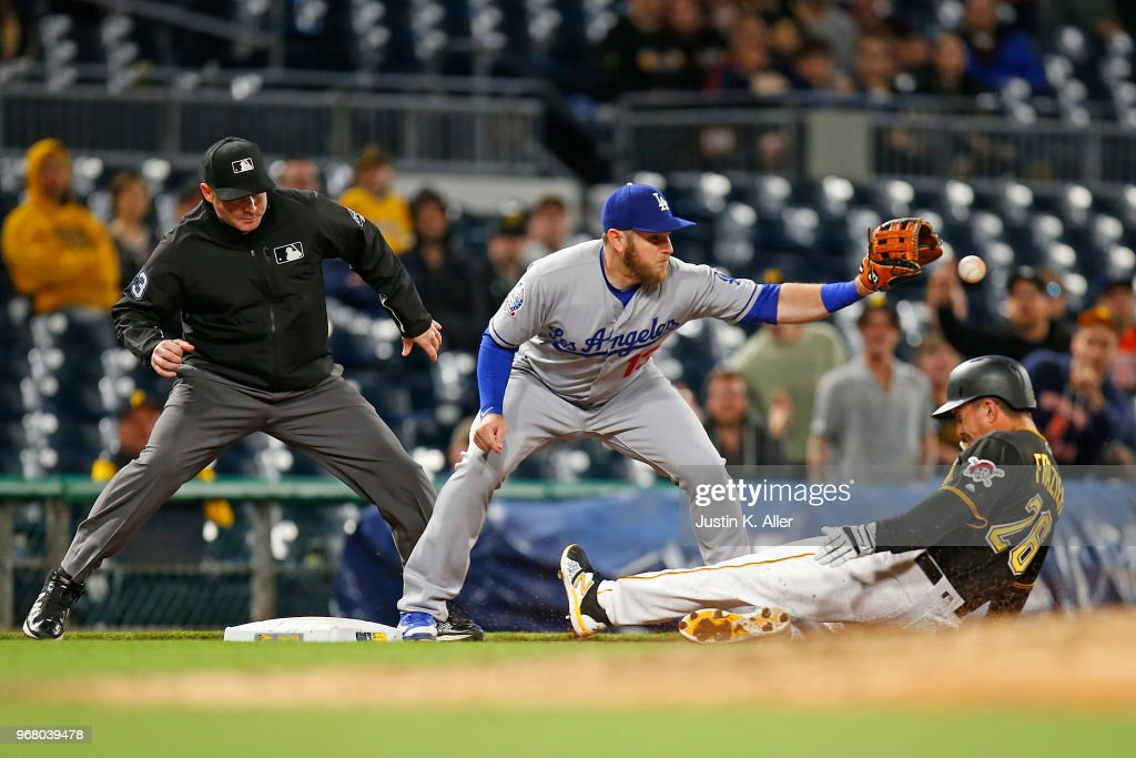 Max Muncy #13 of the Los Angeles Dodgers tags out Adam Frazier #26 of the Pittsburgh Pirates in the eighth inning at PNC Park on June 5, 2018 in Pittsburgh, Pennsylvania.