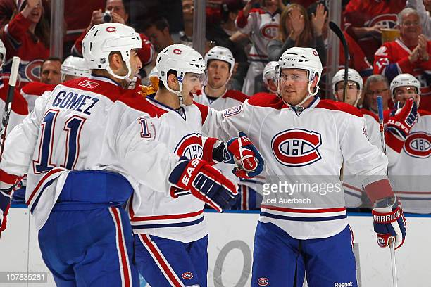 Max Pacioretty is congratulated by Scott Gomez and James Wisniewski of the Montreal Canadiens after scoring a goal against the Florida Panthers in...