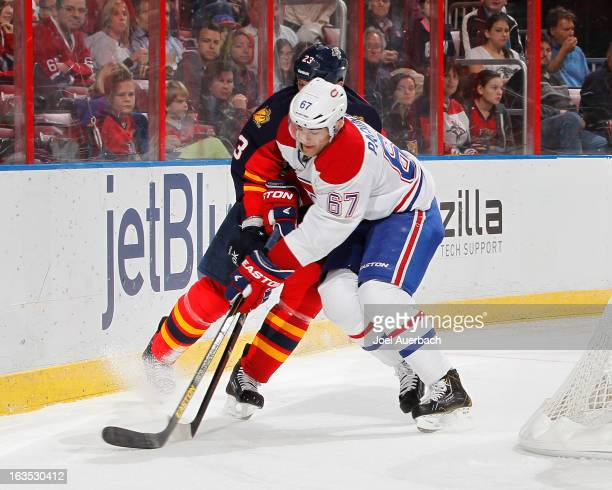 Max Pacioretty of the Montreal Canadiens and Tyson Strachan of the Florida Panthers battle for a loose puck at the BBT Center on March 10 2013 in...