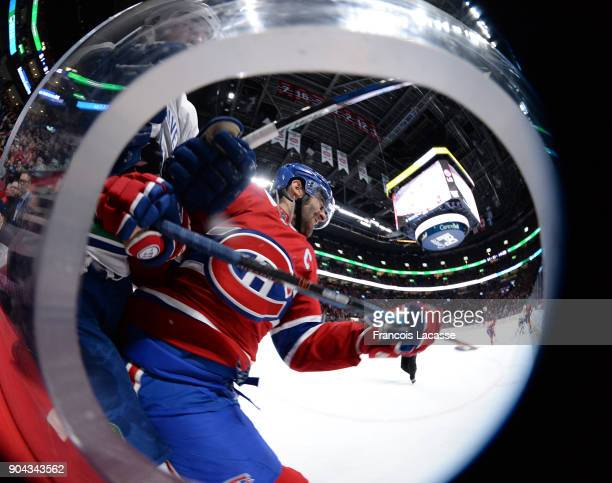 Max Pacioretty of the Montreal Canadiens checks Erik Gudbranson of the Vancouver Canucks in the NHL game at the Bell Centre on January 7 2018 in...
