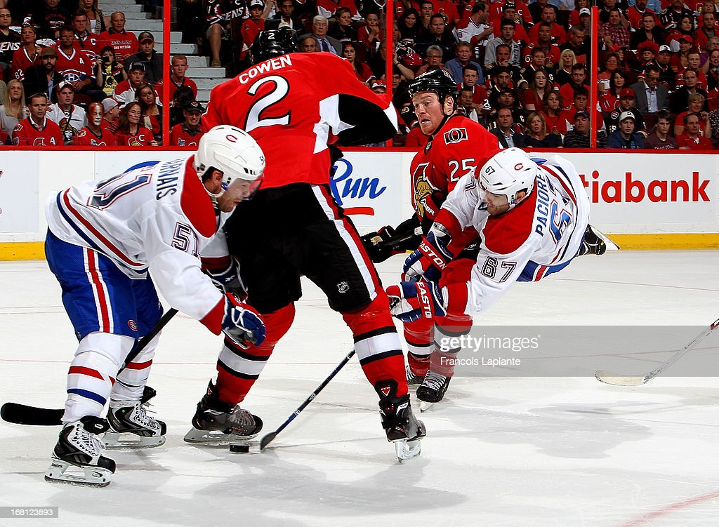 Max Pacioretty #67 of the Montreal Canadiens goes airborne and shoots the puck as Chris Neil #25 and Jared Cowen #2 of the Ottawa Senators defend in Game Three of the Eastern Conference Quarterfinals during the 2013 NHL Stanley Cup Playoffs at Scotiabank Place on May 5, 2013 in Ottawa, Ontario, Canada.