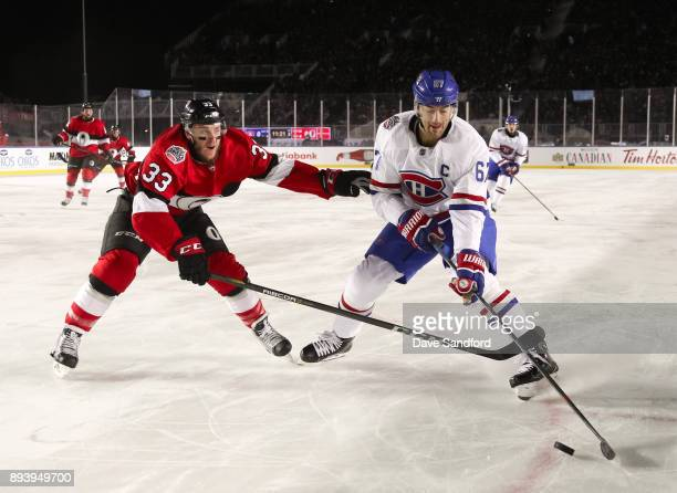 Max Pacioretty of the Montreal Canadiens pulls the puck away from Fredrik Claesson of the Ottawa Senators during the 2017 Scotiabank NHL100 Classic...