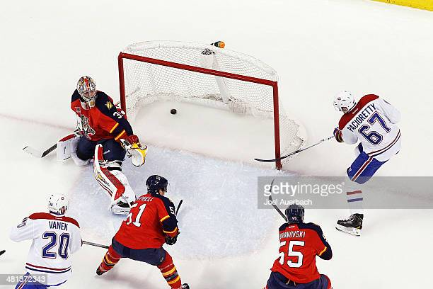 Max Pacioretty of the Montreal Canadiens scores his first goal of the night past goaltender Dan Ellis of the Florida Panthers during first period...