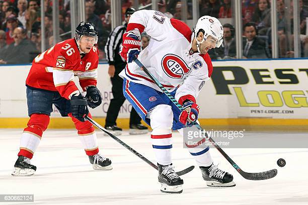 Max Pacioretty of the Montreal Canadiens skates with the puck against Jussi Jokinen of the Florida Panthers at the BBT Center on December 29 2016 in...