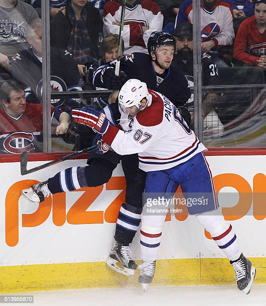 Max Pacioretty of the Montreal Canadiens takes Joshua Morrissey of the Winnipeg Jets to the boards in first period action in an NHL game at the MTS...