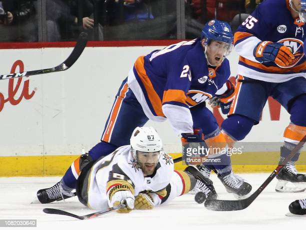 Max Pacioretty of the Vegas Golden Knights attempts to hit the puck as Brock Nelson of the New York Islanders hovers above at the Barclays Center on...
