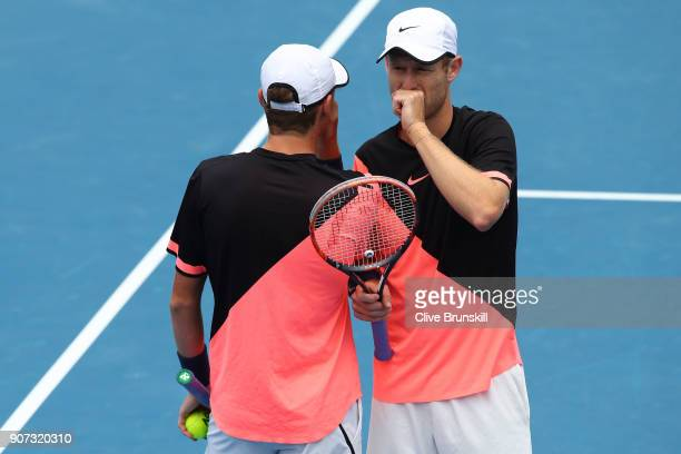 Max Purcell and Luke Saville of Australia talk tactics in their second round men's doubles match against Lukasz Kubot of Poland and Marcelo Melo of...