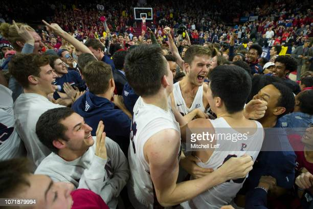Max Rothschild AJ Brodeur and Michael Wang of the Pennsylvania Quakers celebrate their win over the Villanova Wildcats at The Palestra on December 11...