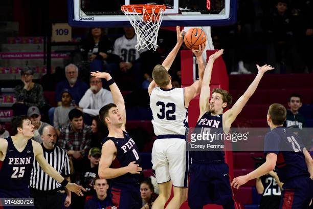 Max Rothschild and Caleb Wood of the Pennsylvania Quakers guard Blake Reynolds of the Yale Bulldogs during the second half at The Palestra on...