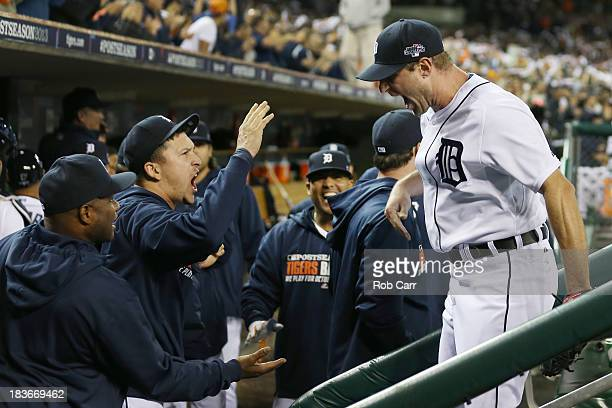 Max Scherzer of the Detroit Tigers celebrates with teammates after getting the third out in the eighth inning against the Oakland Athletics during...