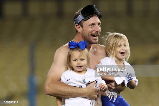 Max Scherzer of the Los Angeles Dodgers celebrates with his daughters Brooklyn and Kacey after they defeated the St. Louis Cardinals 3 to 1 during...