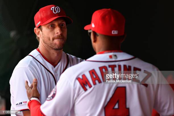 Max Scherzer of the Washington Nationals talks with manager Dave Martinez in the dugout after being removed from the game in the eighth inning...