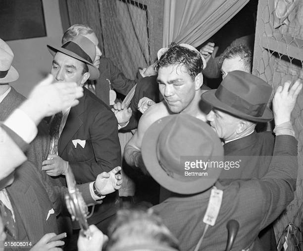 Max Schmeling, former Heavy weight champion, his face badly battered, returns to his dressing room after knocking out the sensation Joe Louis in 2:29...