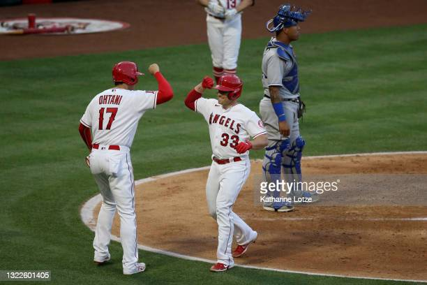 Max Stassi high-fives Shohei Ohtani of the Los Angeles Angels after Stassi's home run in the third inning against the Kansas City Royals at Angel...
