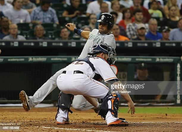 Max Stassi of the Houston Astros cannot make a play at home plate on Franklin Gutierrez of the Seattle Mariners in the third inning of their game at...