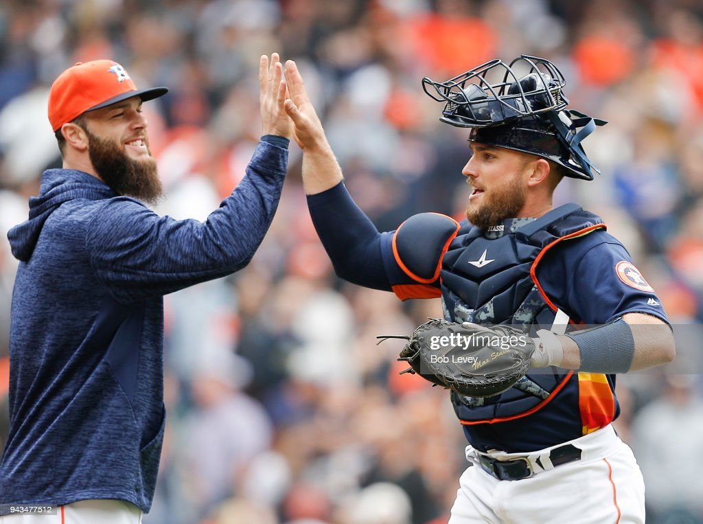 Max Stassi #12 of the Houston Astros (R) high fives Dallas Keuchel #60 after the final out against the San Diego Padres at Minute Maid Park on April 8, 2018 in Houston, Texas.