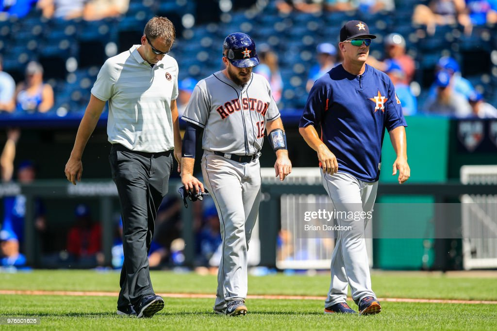 Max Stassi #12 of the Houston Astros walks off the field with training staff and manager AJ Hinch after being taken out of the game in the ninth inning against the Kansas City Royals at Kauffman Stadium on June 16, 2018 in Kansas City, Missouri.