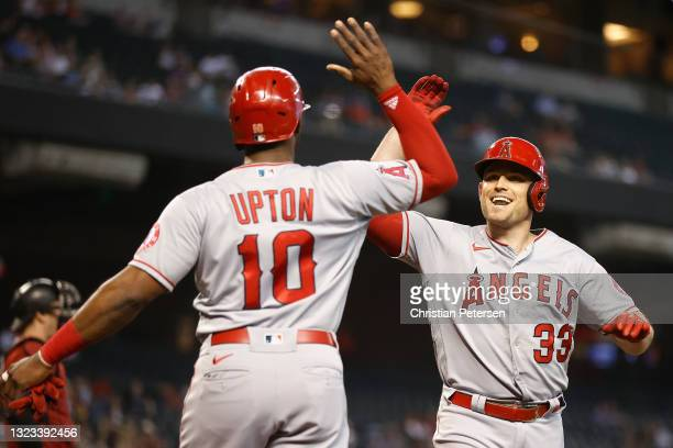 Max Stassi of the Los Angeles Angels high fives Justin Upton after hitting a two-run home run against the Arizona Diamondbacks during the first...