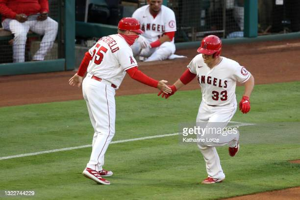 Max Stassi of the Los Angeles Angels high-fives third base coach Brian Butterfield of the Los Angeles Angels as he runs the bases following his home...