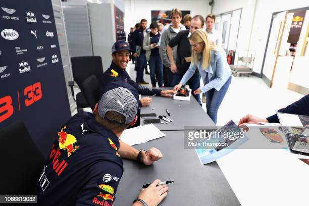 Max Verstappen of Netherlands and Red Bull Racing and Daniel Ricciardo of Australia and Red Bull Racing talk with Red Bull Racing team members during...