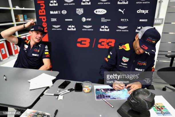 Max Verstappen of Netherlands and Red Bull Racing and Daniel Ricciardo of Australia and Red Bull Racing sign autographs during the Red Bull Racing...