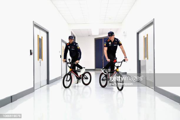 Max Verstappen of Netherlands and Red Bull Racing and Daniel Ricciardo of Australia and Red Bull Racing ride bikes in the factory during the Red Bull...