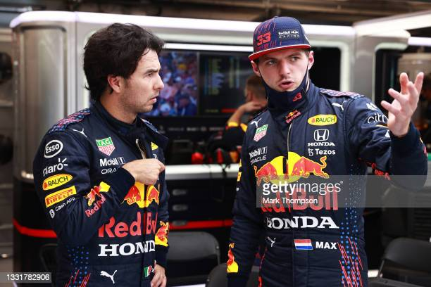 Max Verstappen of Netherlands and Red Bull Racing and Sergio Perez of Mexico and Red Bull Racing talk in the garage during the red flag delay during...