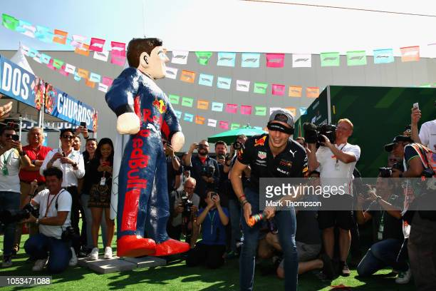 Max Verstappen of Netherlands and Red Bull Racing attempts to smash a pinata in the Paddock during previews ahead of the Formula One Grand Prix of...