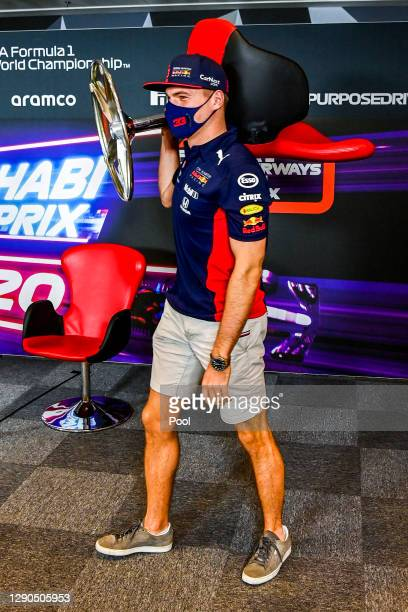 Max Verstappen of Netherlands and Red Bull Racing carries a chair in the Drivers Press Conference during previews ahead of the F1 Grand Prix of Abu...