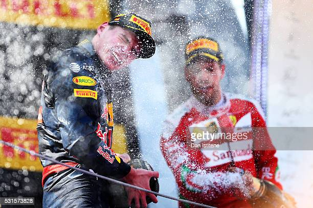 Max Verstappen of Netherlands and Red Bull Racing celebrates his first win on the podium with Sebastian Vettel of Germany and Ferrari during the...