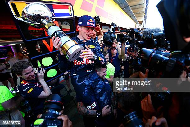 Max Verstappen of Netherlands and Red Bull Racing celebrates with the team in the pit lane after winning his first F1 race at the Spanish Formula One...