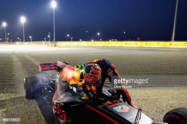 Max Verstappen of Netherlands and Red Bull Racing climbs out of his car after crashing into a barrier during the Bahrain Formula One Grand Prix at...
