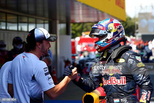 Max Verstappen of Netherlands and Red Bull Racing is congratulated on his first F1 win by Fernando Alonso of Spain and McLaren Honda in parc ferme...