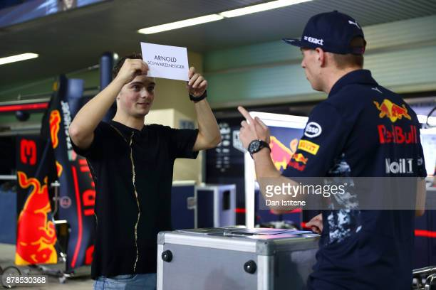 Max Verstappen of Netherlands and Red Bull Racing plays a game of Guess Who with superstar DJ Martin Garrix after practice for the Abu Dhabi Formula...
