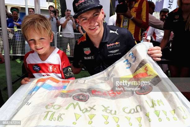 Max Verstappen of Netherlands and Red Bull Racing poses for a photo with a young fan during final practice for the Bahrain Formula One Grand Prix at...