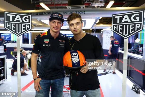 Max Verstappen of Netherlands and Red Bull Racing presents superstar DJ Martin Garrix with a racing helmet after practice for the Abu Dhabi Formula...