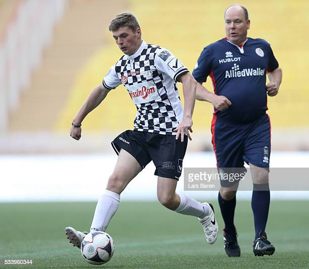 Max Verstappen of Netherlands and Red Bull Racing runs with the ball next to Prince Albert of Monaco during the 24th World Stars football match at...