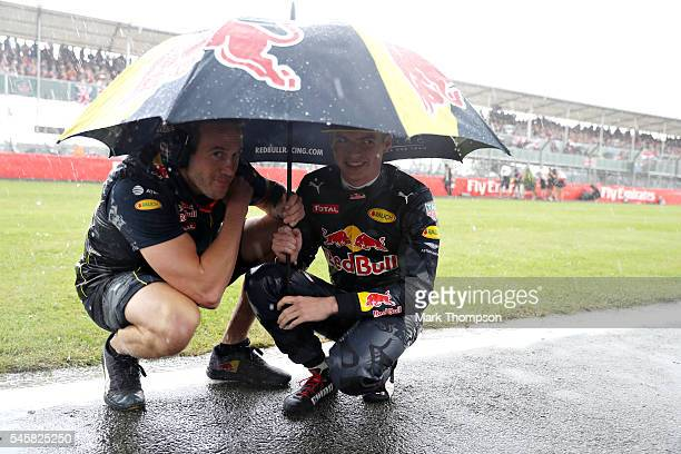 Max Verstappen of Netherlands and Red Bull Racing shelters from the rain on the grid before the Formula One Grand Prix of Great Britain at...